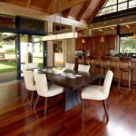 Tropical Open Concept Kitchen Dark Wooden Kitchen Table And White Chairs Wooden Bar Stool Medium Toned Wooden Floors Floating Cabinets