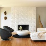 Two Black Chairs With Stainless Steel Base Round Top Center Table In White Round Black Area Rug White Sectional With Facing Chaise Medium Toned Wood Floors Fireplace With Patterned Concrete Surround