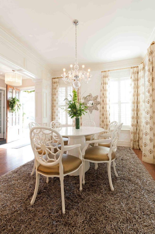 white French provincial dining chairs with gold toned upholstered seating white round dining table crystal chandelier grey area rug dark hardwood floors