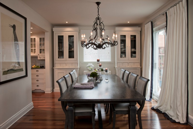 white finishing corner cabinets dark grey dining chairs dark finished dining table lovely black chandelier dark toned wood floors white draperies with black decorative line