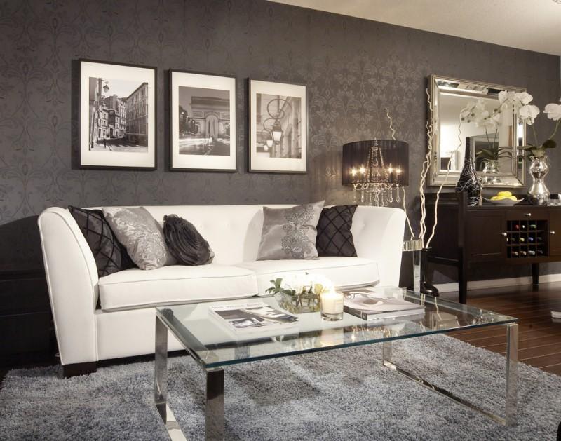 white sofa with black accent pillows rectangular glass top center table light grey shag carpet black wallpaper with dark motifs