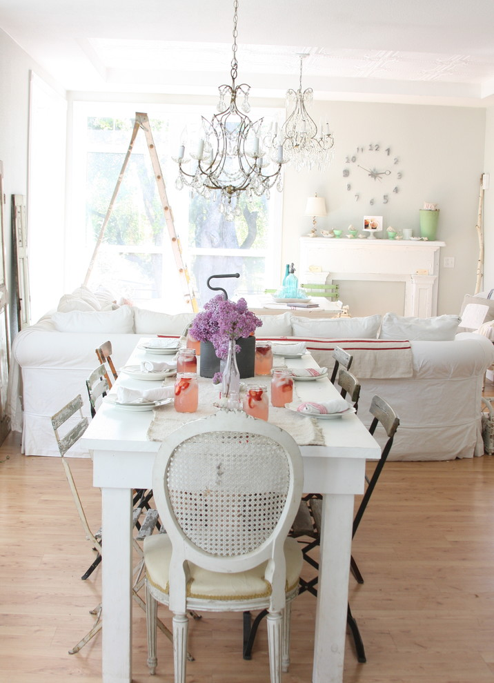 white transitional dining room idea white French dining chair some industrial dining chairs medium toned wood floors classic chandelier
