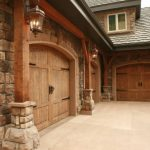 Wooden Garage Door Wooden Trim Wooden Pillars Garage Pulls Stone Siding Garage Lamp Grey Roof