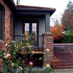 Brick House In Red Brown Color With Wooden Deck Dark Stained Auburn Beige Painted Wall Porch Table Sets Black Trim Brass Exterior Lamp Cover