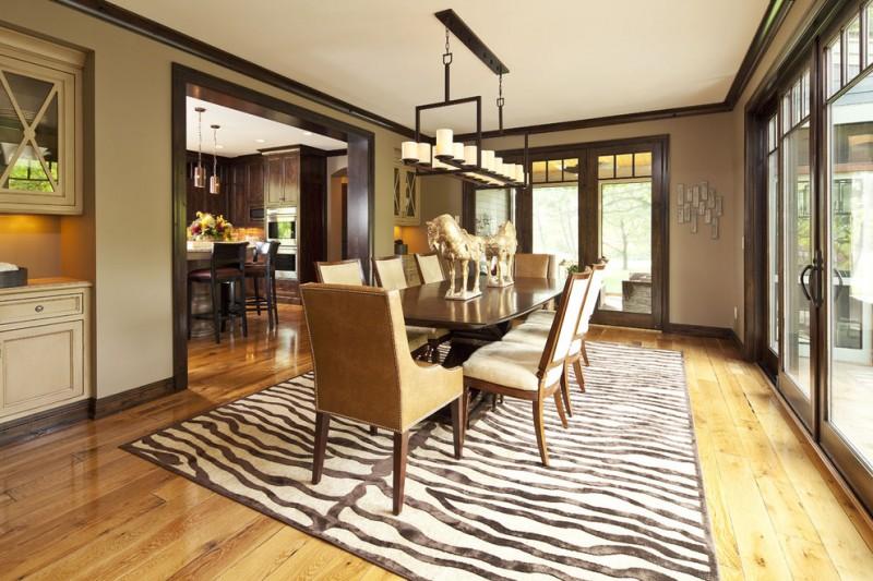 Contemporary enclosed dining room idea with beige walls and medium tone hardwood floors zebra striped rug pendant lamp animal statues