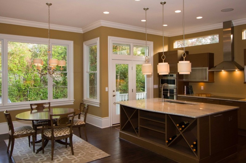 Contemporary kitchen with flat panel cabinets, dark wood cabinets and stainless steel appliances pendant lamps marble countertops golden wall in white trim