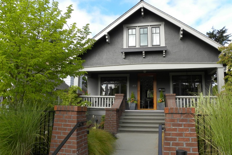 Craftsman gray two story exterior home with a gable roof stair way path with bricks posts glass door in brown trim glass windows in white trim