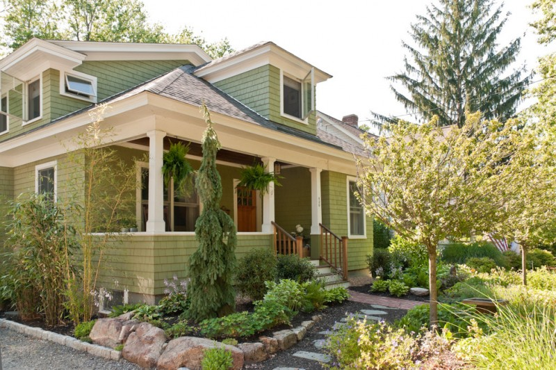 Craftsman green exterior home idea white trim glass windows stone slabs pathways stone for gardening area stair front porch wooden fences