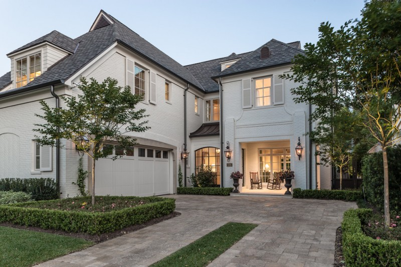 Elegant white brick exterior home with white doors and windows, dark gray roofs front porch wooden chairs brass exterior lamp cover
