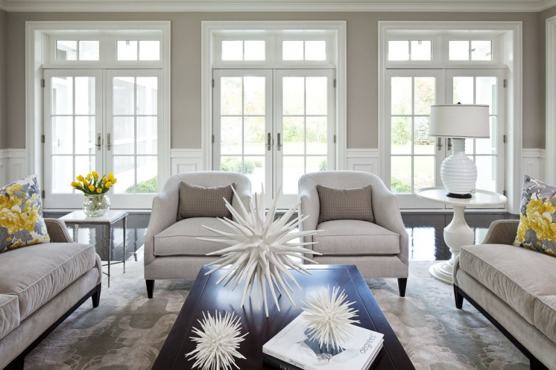 Expansive transitional formal open concept living room with gray walls white couch gray pillow throws wooden coffee table gray carpet medium toned wooden floors