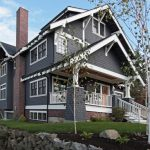 Large Arts And Crafts Blue Three Story Wood Exterior Home Gray Painted Brick Wall And Wooden Deck Wall Brown Front Door And Glass Windows In White Trim White Fences