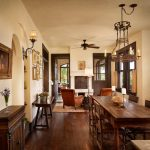 Mediterranean Dining Room With Beige Walls And Dark Hardwood Floors Pendant Lamp Brass Ceiling Fan Accent Rug Wooden Cabinets Black Painted Wooden Door