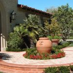 Mediterranean Front Yard Landscape With A Container Garden And Brown And Cream Brick Pavers Exposed Stone Mortar Wall Wooden Front Door