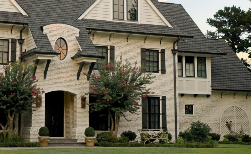 Mid sized elegant beige three story white painted brick exterior home with a gable roof and a shingle roof dark painted front doors glass windows in dark trim