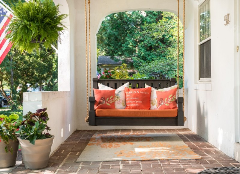 Tuscan style front porch idea hanging swing in grey orange throw pillows brick pavers for floors