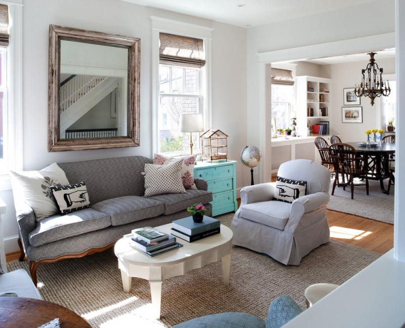 airy and warm feel living room white chair slipcover grey sofa with hand crafted wood legs grey rug wood floors aqua toned side table with drawer system