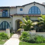 Arched Window Arched Door Tiled Roof Blue Trim Iron Fence Front Yard Small Balcony Path Way Ceiling Lamp Wall Mounted Lanterns Palm Trees