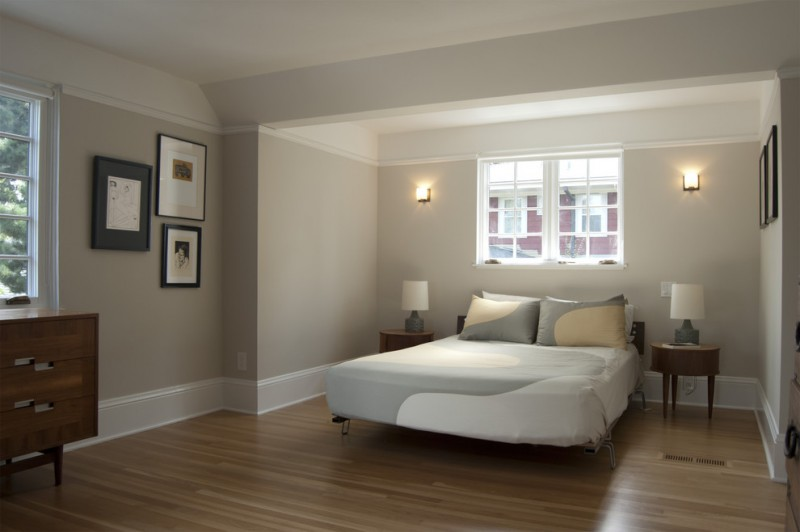 bedroom with light toned wooden floors wooden cabinet table lamps wooden table sconces beige wall white painted oak trim wall artworks