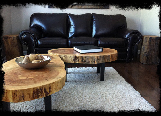black leather sofa large modern tree trunk coffee tables white wool area rug dark toned wood floors tree trunk side tables