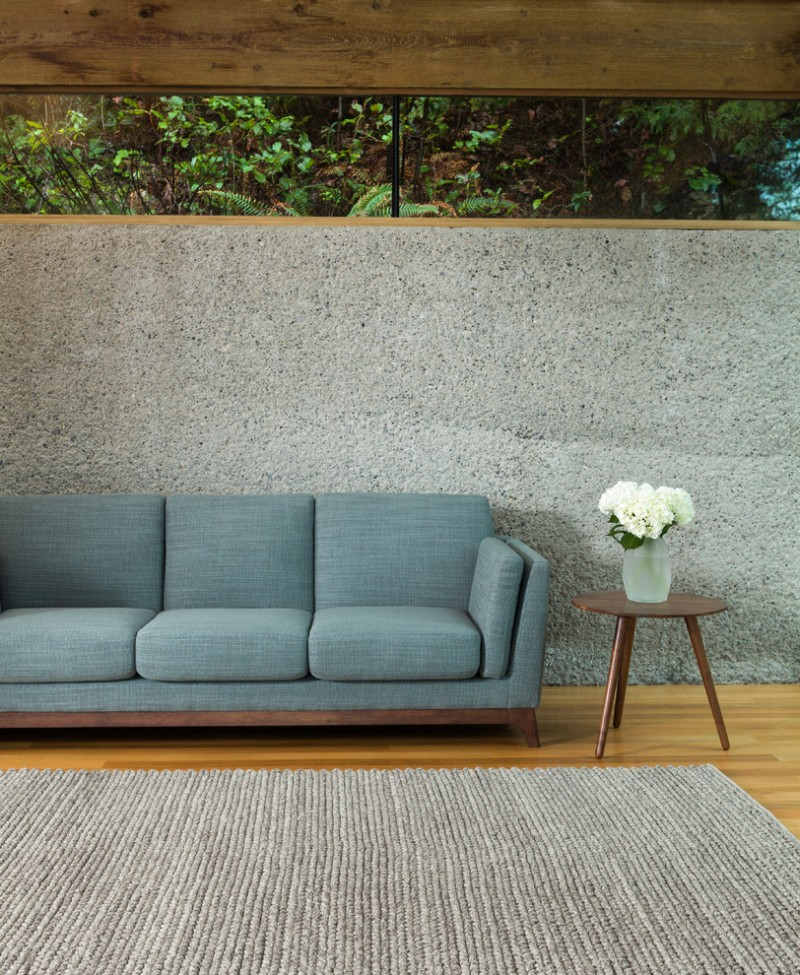 blue sectional sofa with crafted wood construction round shaped wood top side table with slanted legs textured grey area rug concrete walls with upper glass window