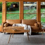 Brown Leather Sofa With Tufted Seating And Armrests Asymmetric Wood Top Coffee Table With Slanted Legs Textured And Grey Wool Area Rug Modern Black Floor Lamp