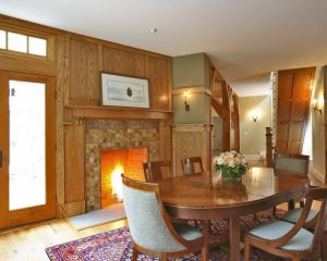 classic dining room with a tile fireplace surround oak wall and trim wooden dining room sets geometric carpets light toned wooden floors