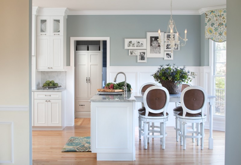 classic eat in kitchen with a farmhouse sink, recessed panel cabinets, white cabinets, white backsplash, stone tile backsplash, granite countertops and light hardwood floors