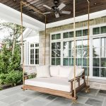 Classic Front Porch Idea Wood Swinging Daybed White Throw Pillows White Mattress Stone Paving Floors Dark Finished Wood Ceilings Ceiling Fan