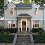 Classic Gray Exterior Home With Evergreen Shrubs Stairs Pathway Brick Wall Gray Wall Glass Windows In White Trim Gray Front Door And Roofs