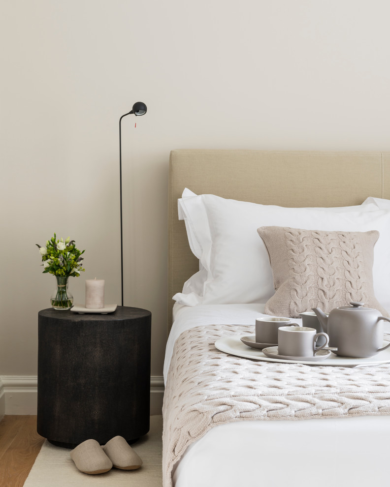 clean lines bedroom set with beige headboard white and soft neutral bedding treatment black doffs tree trunk bedside table white candle holder