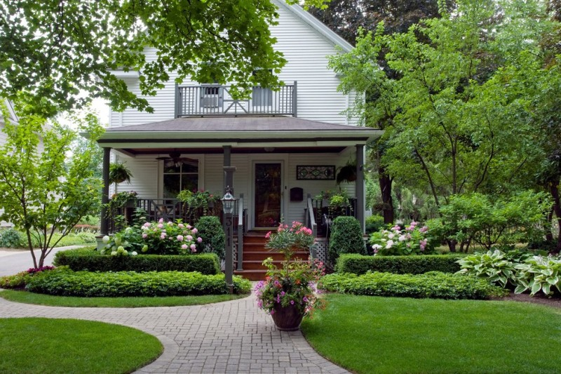 concrete tiles pathway white painted wooden deck black posts glass front door and windows in white trim front stairs wooden fences green shrubbery