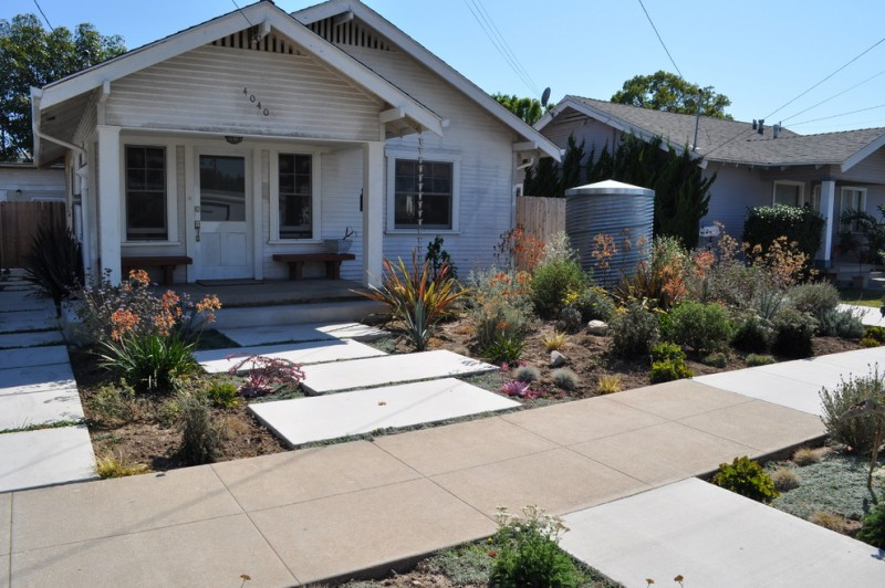 contemporary front yard drought tolerant landscape with galvanized metal barrel concrete pathways white painted wooden deck wall wooden porch benches glass front door and windows