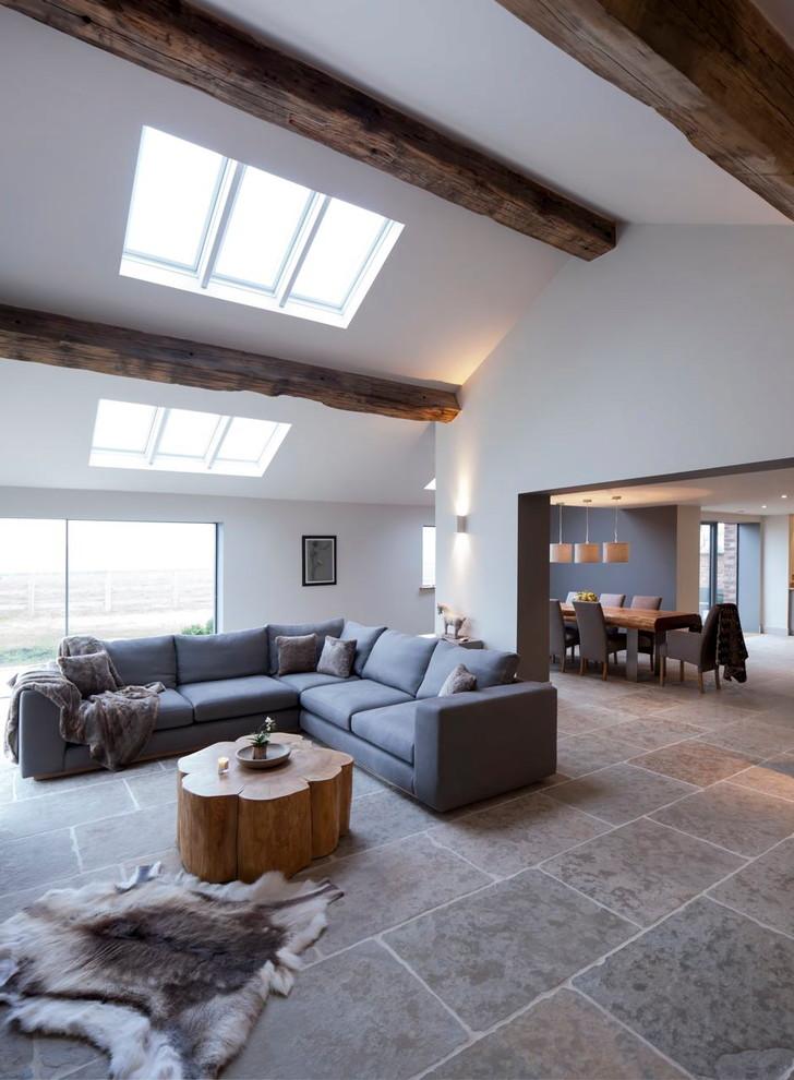 corner sectional sofa in grey dark accent pillows flower like tree trunk coffee table grey tiles floors dark exposed beams