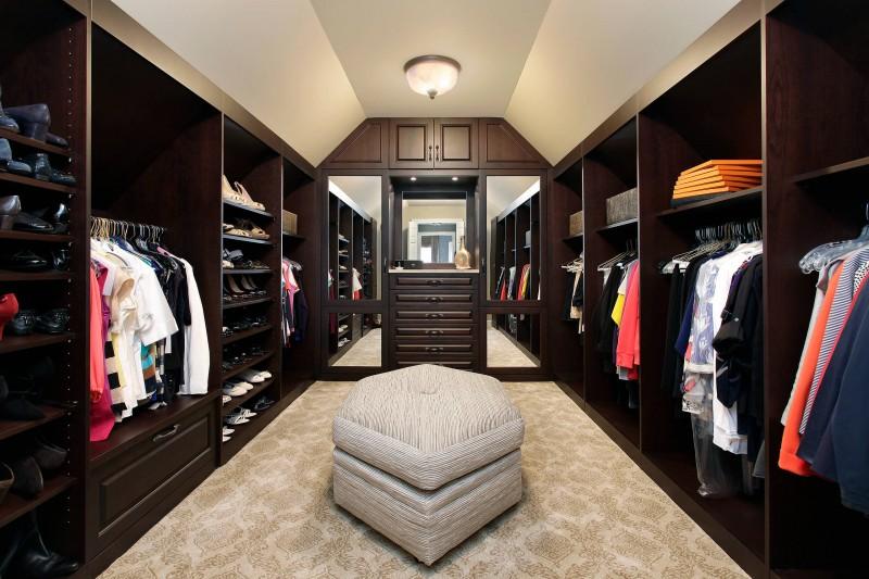 dark cabinet built in cabinet mirrored cabinet open shelves shoe shelf ottoman carpeted floor ceiling lamp
