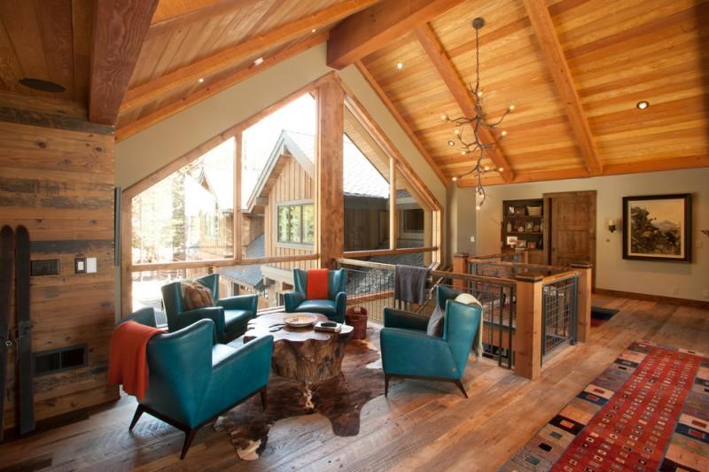 deep turquoise mid century modern chairs dark toned tree trunk table dark toned wood floors slanted wood ceilings