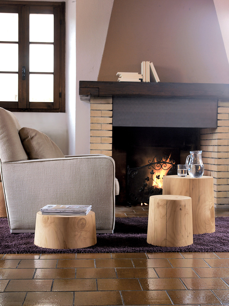different height level tree trunk tables an armchair in grey fireplace with bricks surrounds terracotta tiles floors dark toned shag rug