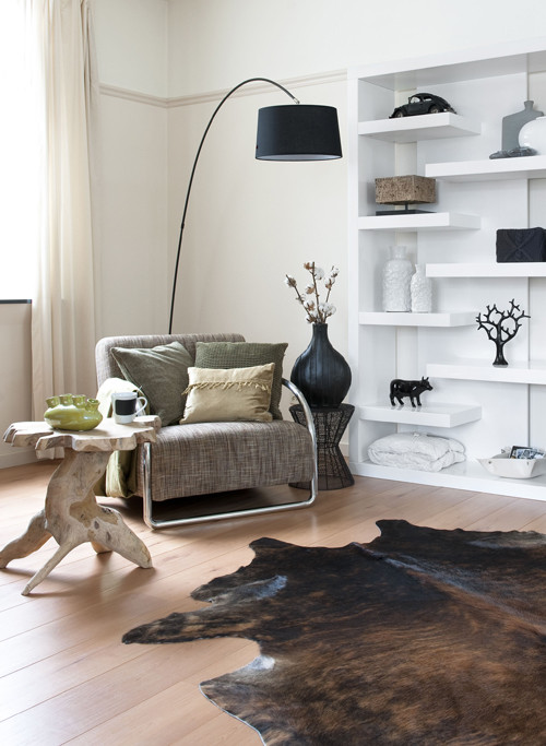 eclectic living room idea cowhide area rug modern sofa with colorful chair modern white shelving unit modern black floor lamp tree trunk coffee table medium toned wood floors