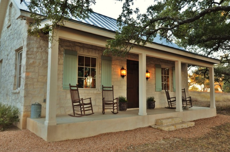 farmhouse front porch idea dark finished rocking chairs light blue window shutters a pair of wall lighting fixtures concrete floors natural stone pavers for walls