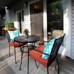 Farmhouse Front Porch Idea Industrial Style Chairs Orang Seating Comforter Multicolored Accent Pillows Round Top Center Table With Higher Legs