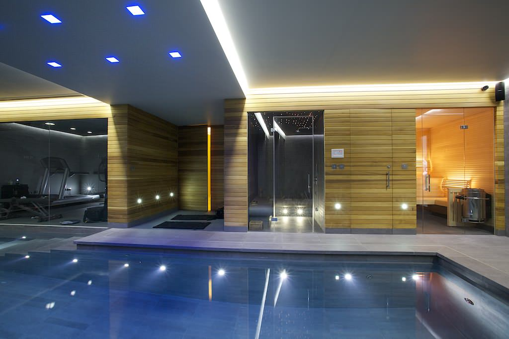 indoor pool grey tiled lined wall gym area home spa recessed lights high raised ceiling