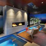 Indoor Pool Wooden Deck Hot Tub Space Orange Table Armchair Orange Side Table Gas Fireplace Recessed Lights Covered Patio
