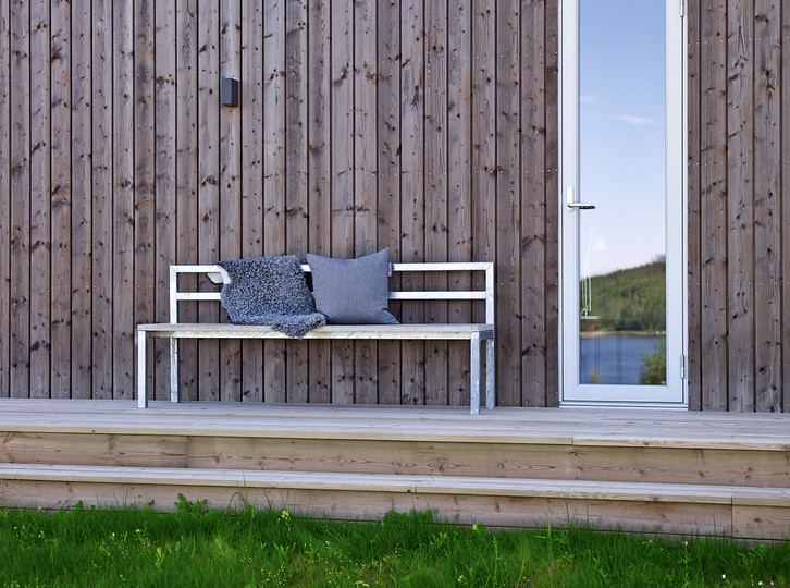 industrial & urban style front porch idea long metal chair grey accent pillow grey blanket wood boards exterior walls wood boards floors narrow front door with glass panel