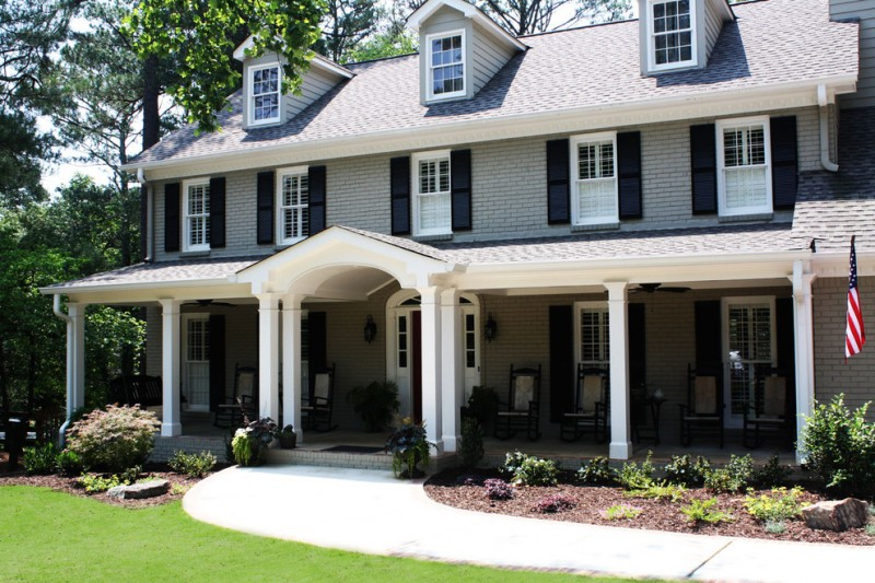 large timeless gray three story wood exterior home with shrubs and curb appeal glass window in white trim white door front porch wooden chairs