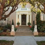 Large Traditional Partial Sun Front Yard Landscape With A Garden Path And Concrete Pavers For Fall White Foo Dogs Beige Wall Black Front Door And White Trim