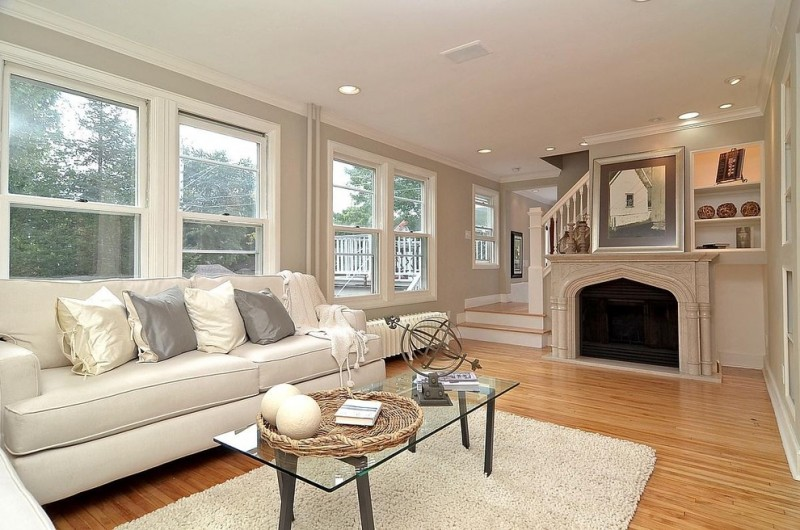living room with white sofa white and black pillow throws light toned wooden floors fireplace glass coffee table beige carpet