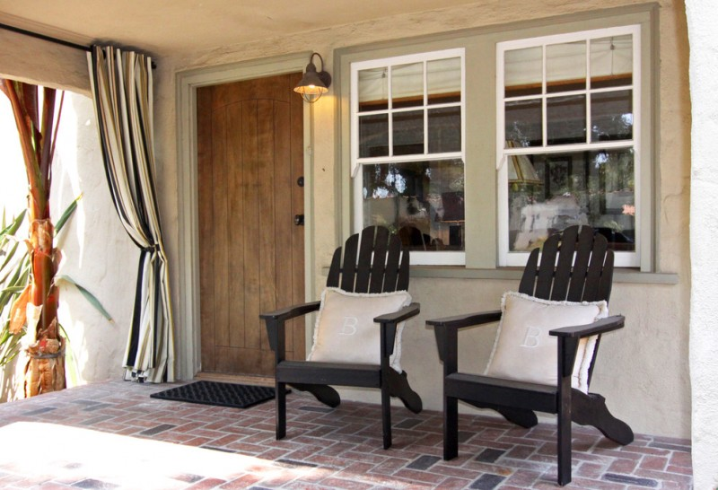 mediteranean front porch idea solid black wood chairs white accent pillows brick paving floors hardwood entrance door