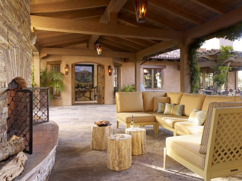 mediterranean patio L shaped chairs in cream multicolored throw pillows three units of tree trunk coffee tables slanted floors