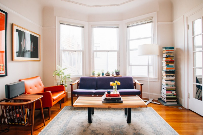 mid century living room with modern appeal orange leather sofa with tufted details grey sofa with wood frame wood boards top coffee table with black legs medium toned wood floors a book tower