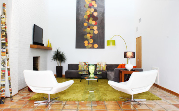 mid century modern living room black velvet sectional sofa multicolored accent pillows modern white lounge chairs green grass rug terracotta floors wood side table floating media console
