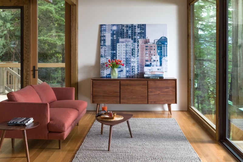 mid century modern living room bold maroon loveseat with higher armrests and slating legs round top side table in dark color grey wool area rug vintage entry table with skycraper painting on its top